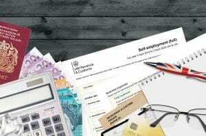 English Tax form sa103 Self-employment from HM revenue and customs lies on table with office items