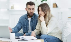 Worried family managing finances on laptop at home